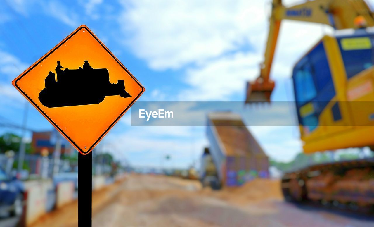 Focus on excavator warning road sign and blurred background of backhoe is working in road construction site area in industrial and development concept Road Signal Warning Warning Symbol Warning Sign Road Warning Sign Close-up Sky Road Road Sign EyeEm Selects Yellow Sign Communication Cloud - Sky Outdoors Transportation Symbol Focus On Foreground Day Mode Of Transportation Land Backhoe Excavator Truck Sand Improvement Barrier Heavy Icon Orange Color Project Industry Highway Street Verhicle Cityscape Urban Skyline