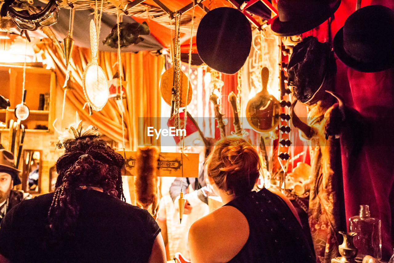 rear view, illuminated, real people, indoors, night, men, hanging, celebration, two people, women, people