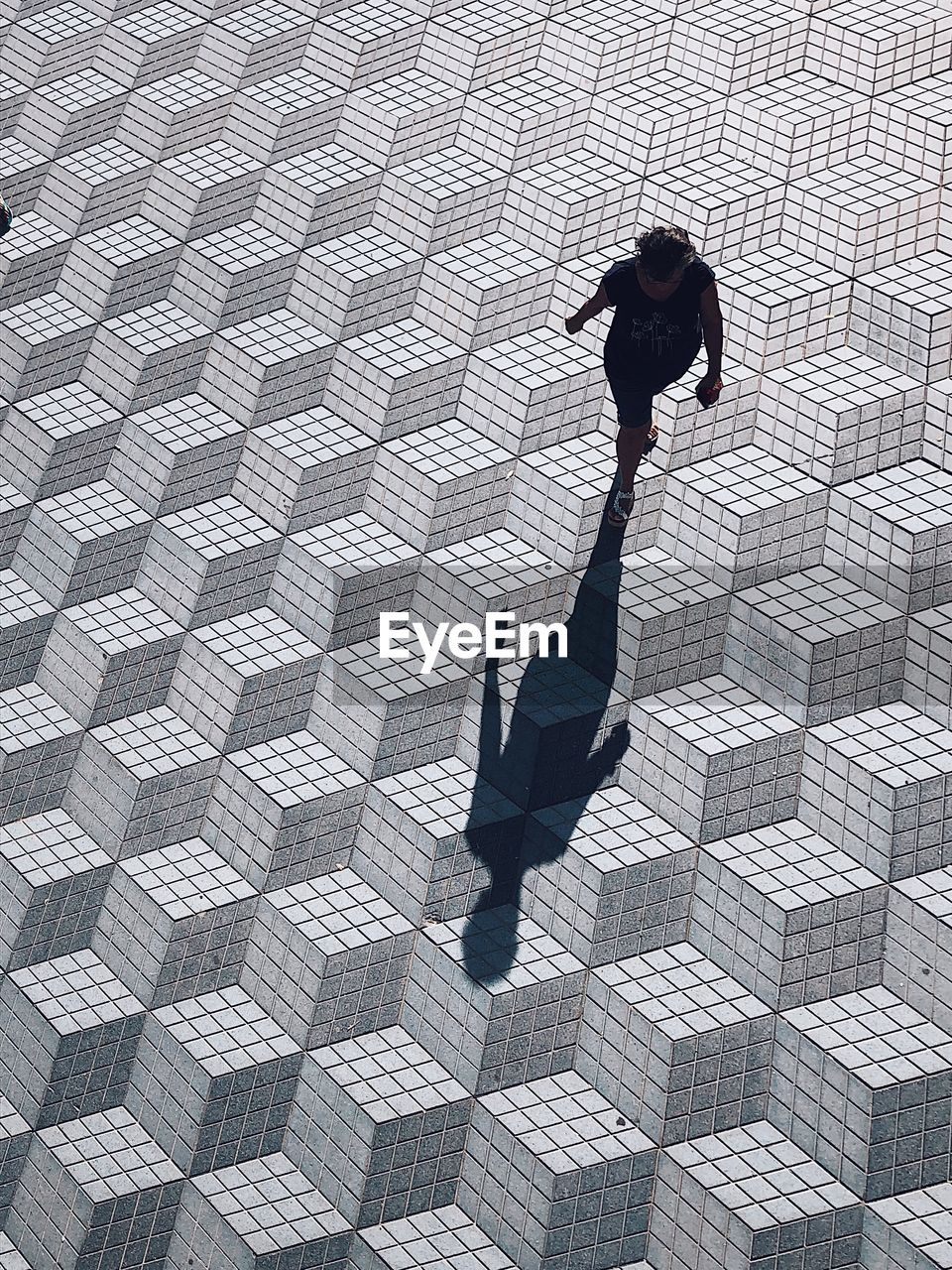 HIGH ANGLE VIEW OF MAN WITH SHADOW ON STREET
