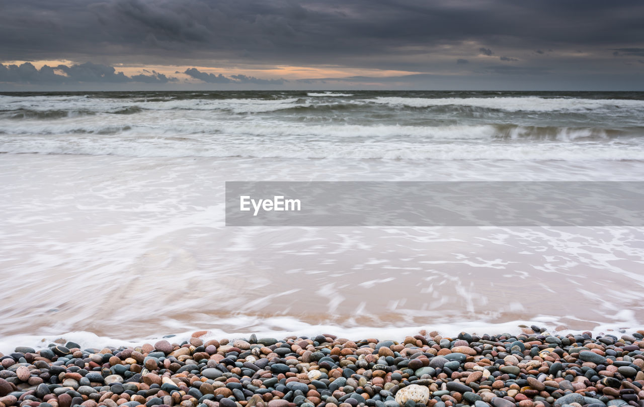 beach, water, sea, land, sky, beauty in nature, scenics - nature, nature, rock, motion, pebble, wave, cloud - sky, solid, stone - object, surfing, tranquility, aquatic sport, stone, horizon over water, outdoors