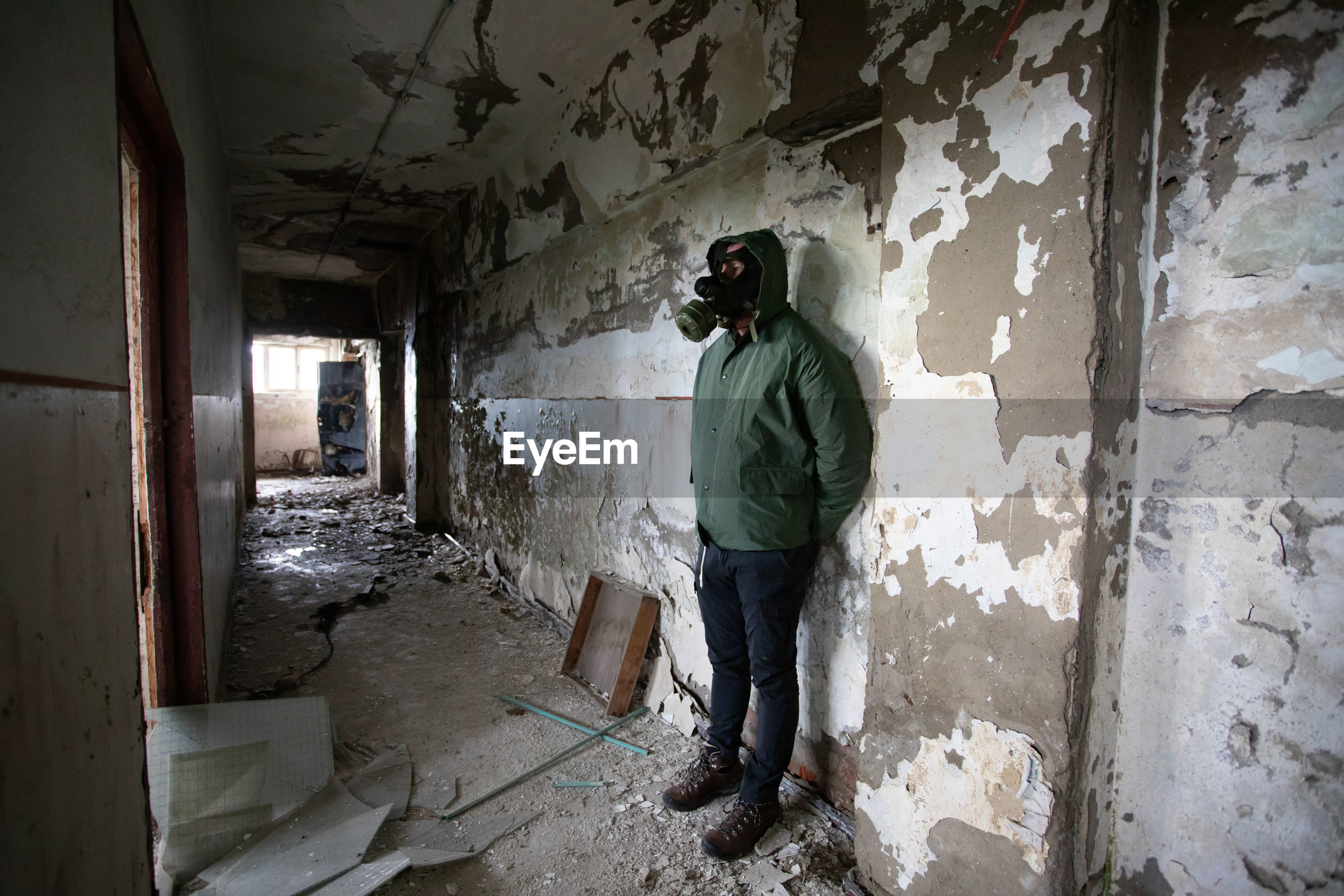 Man wearing gas mask standing in abandoned building