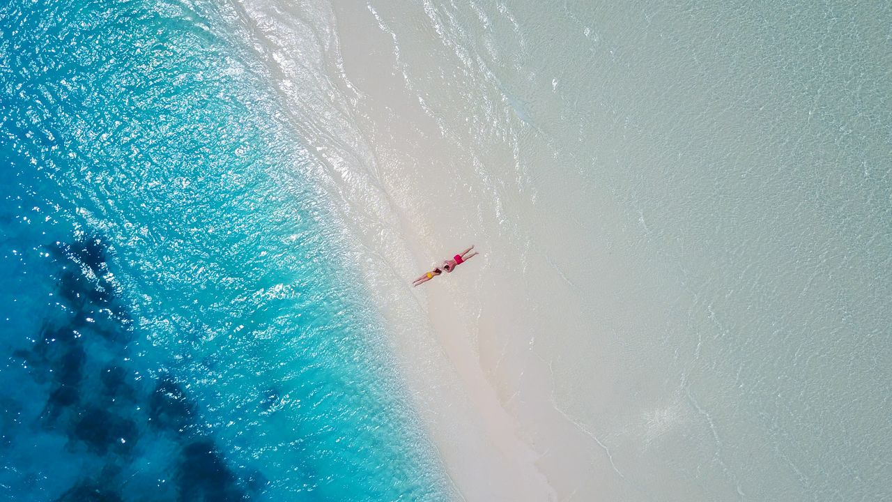 Aerial View Of Couple Relaxing At Beach