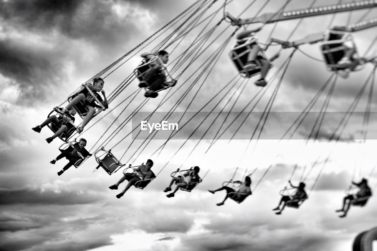 Low Angle View Of Boys Sitting On Chain Swing Ride At Amusement Park