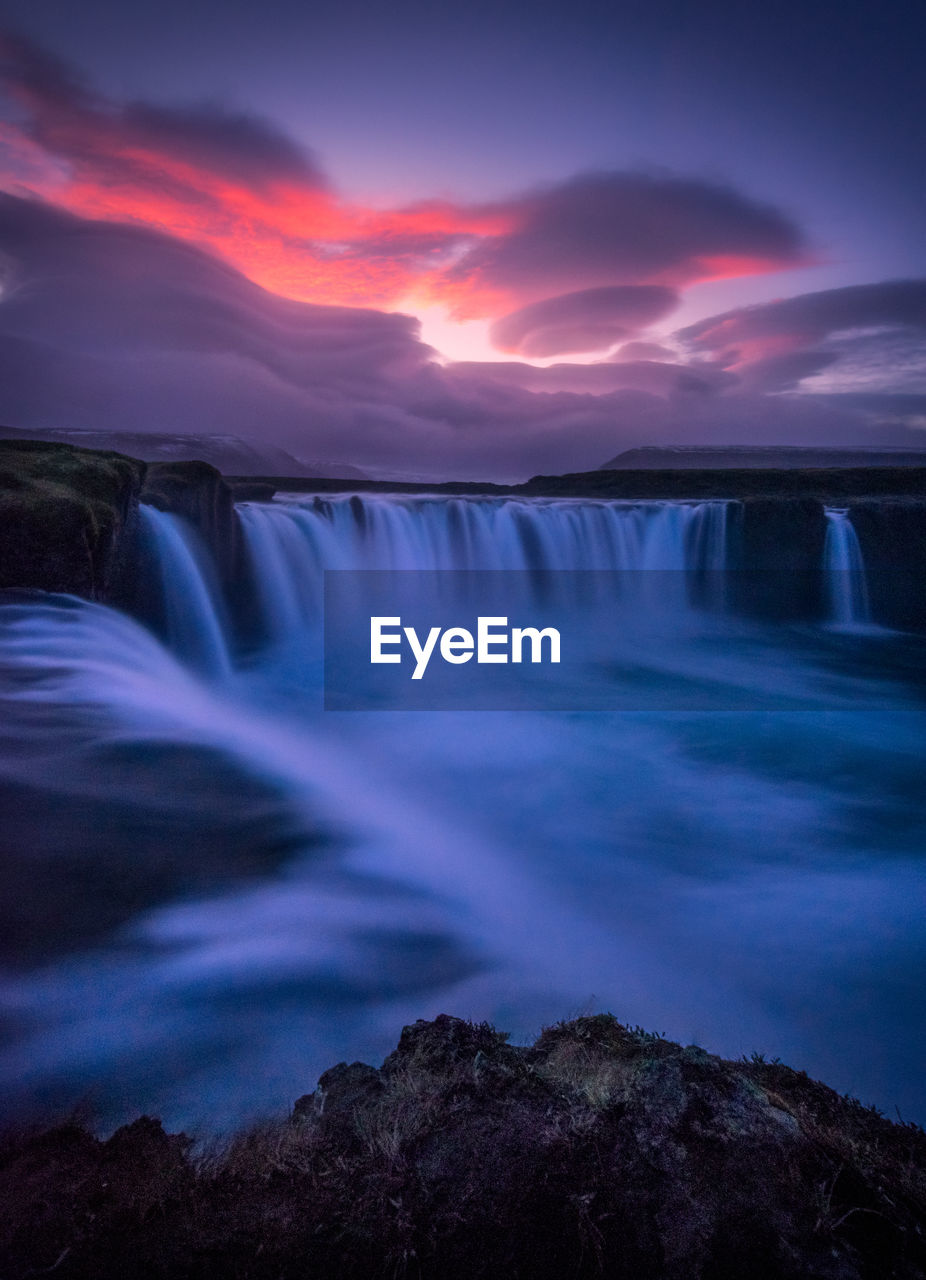 Scenic View Of Waterfall Against Dramatic Sky During Sunset