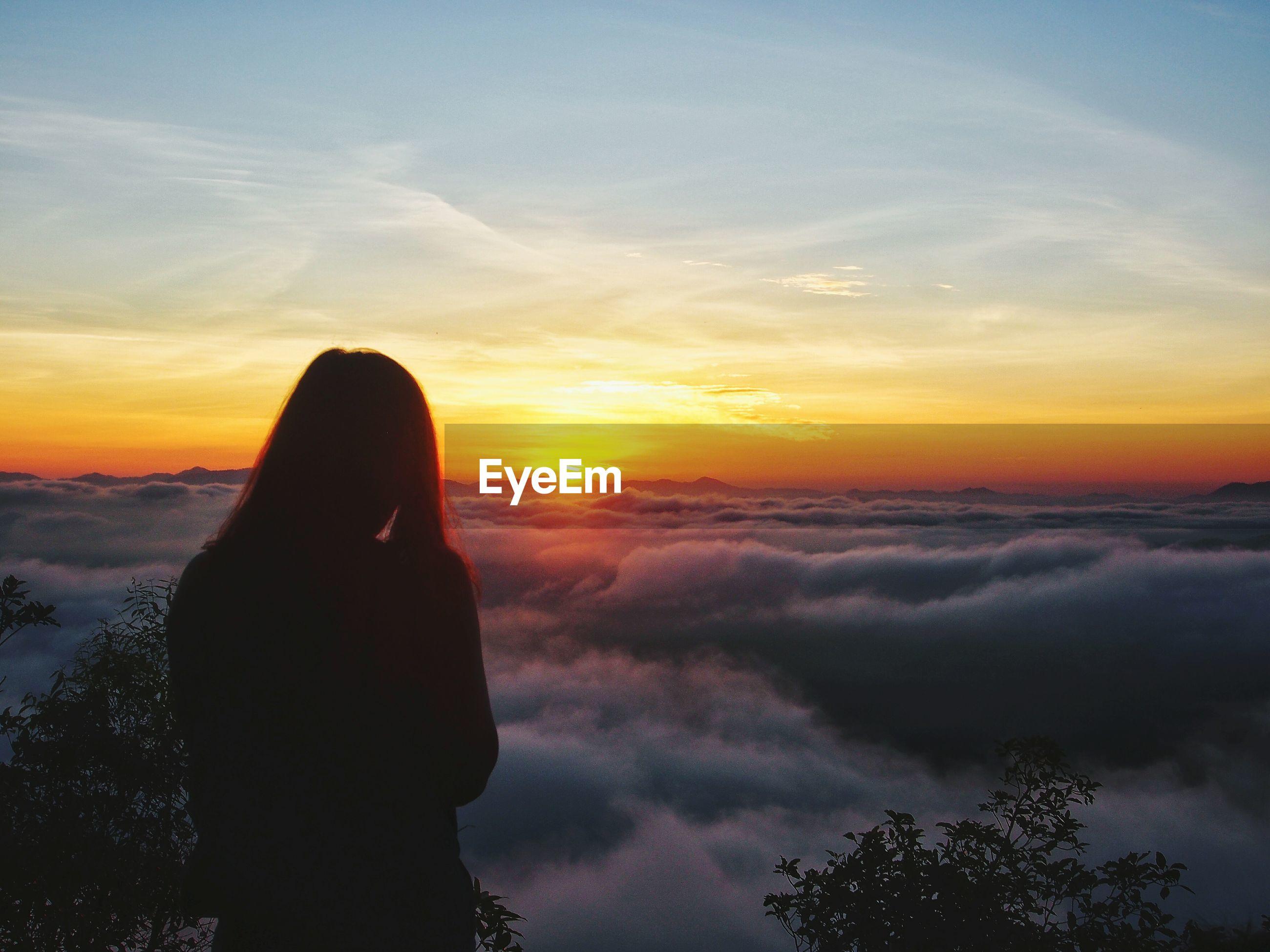 Silhouette girl against orange sky