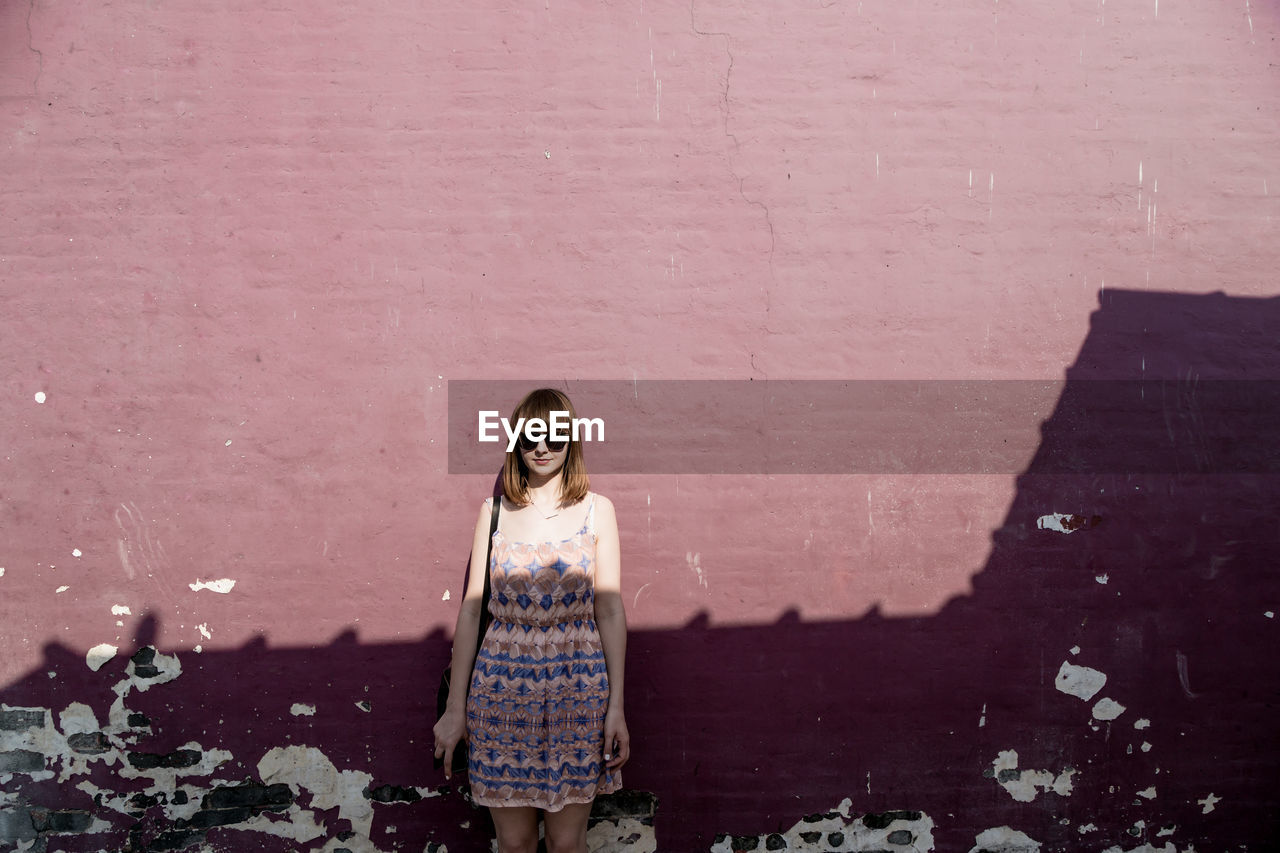 Young Woman Wearing Sunglasses Standing Against Wall