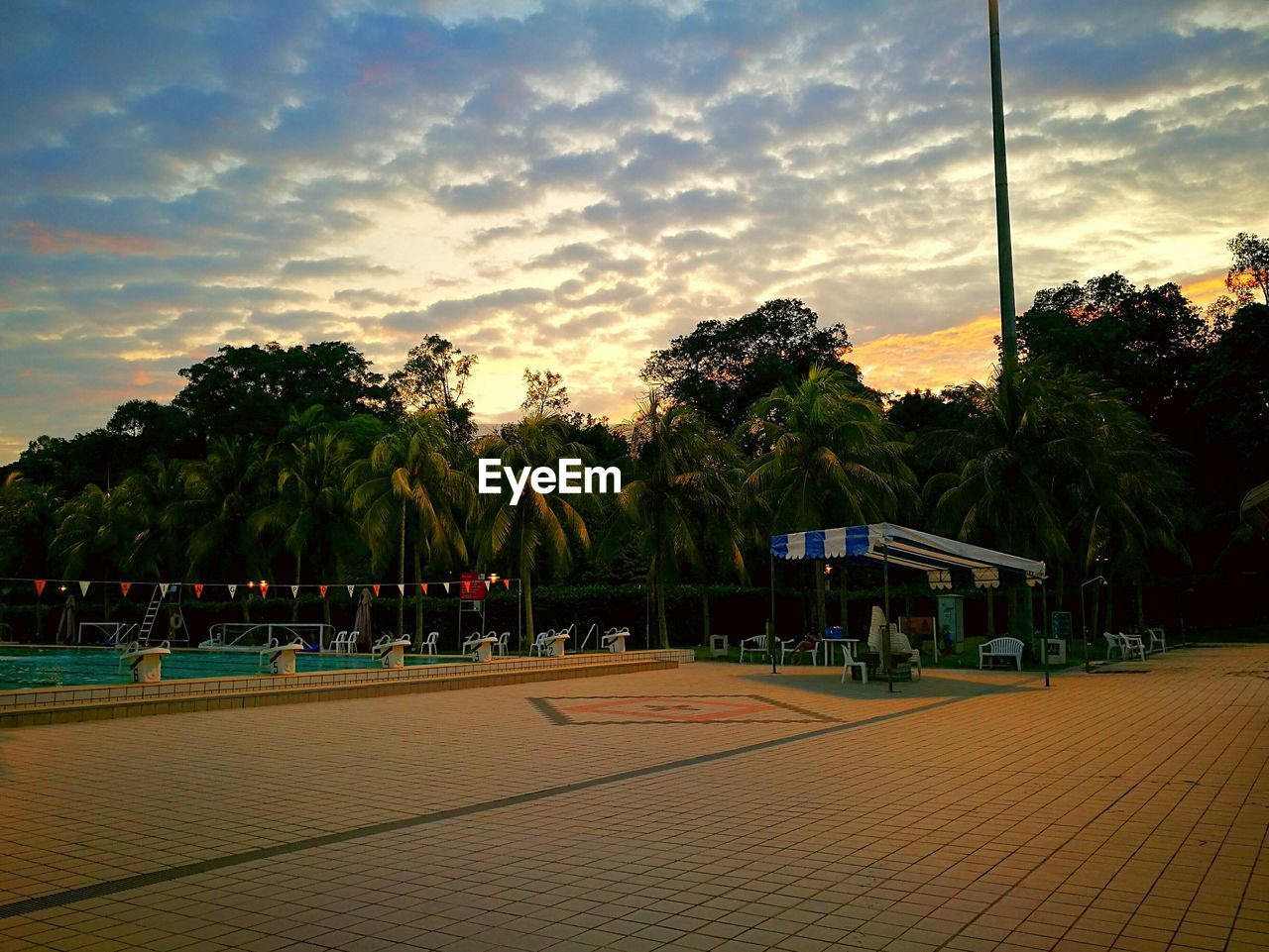 Swimming pool by trees against sky during sunset