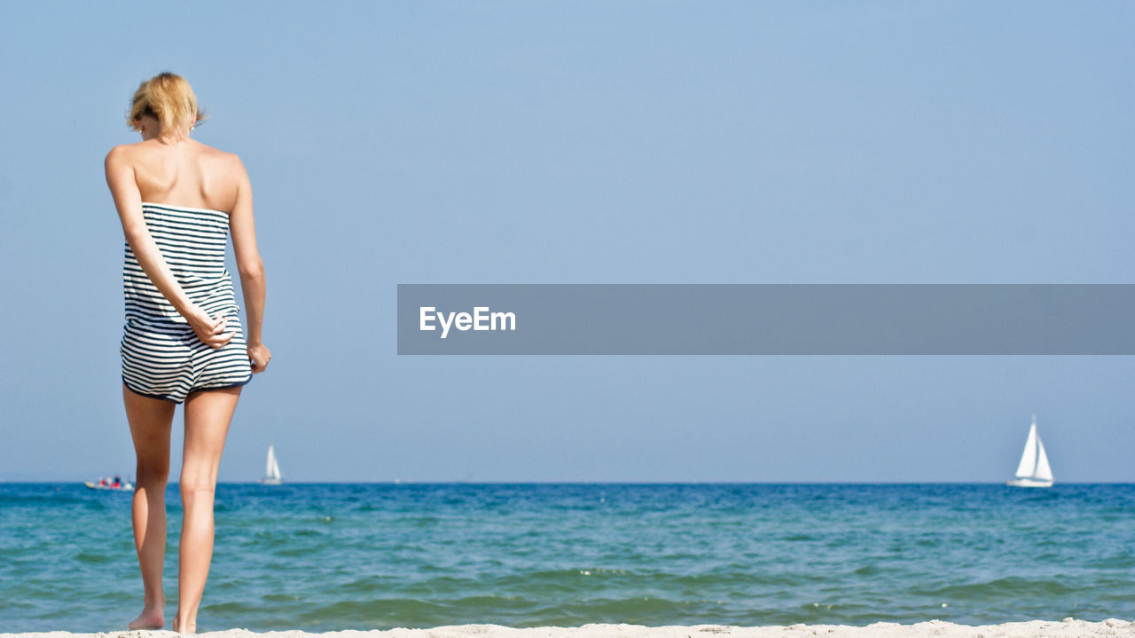 Full Length Of Woman Standing In Water At Beach Against Clear Sky