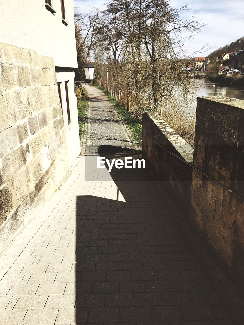 High Angle View Of Footpath By River During Sunny Day
