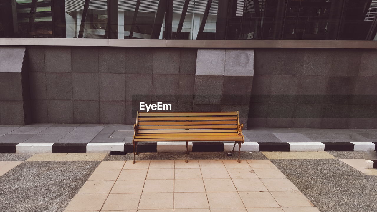 Empty Bench By Sidewalk Against Building In City