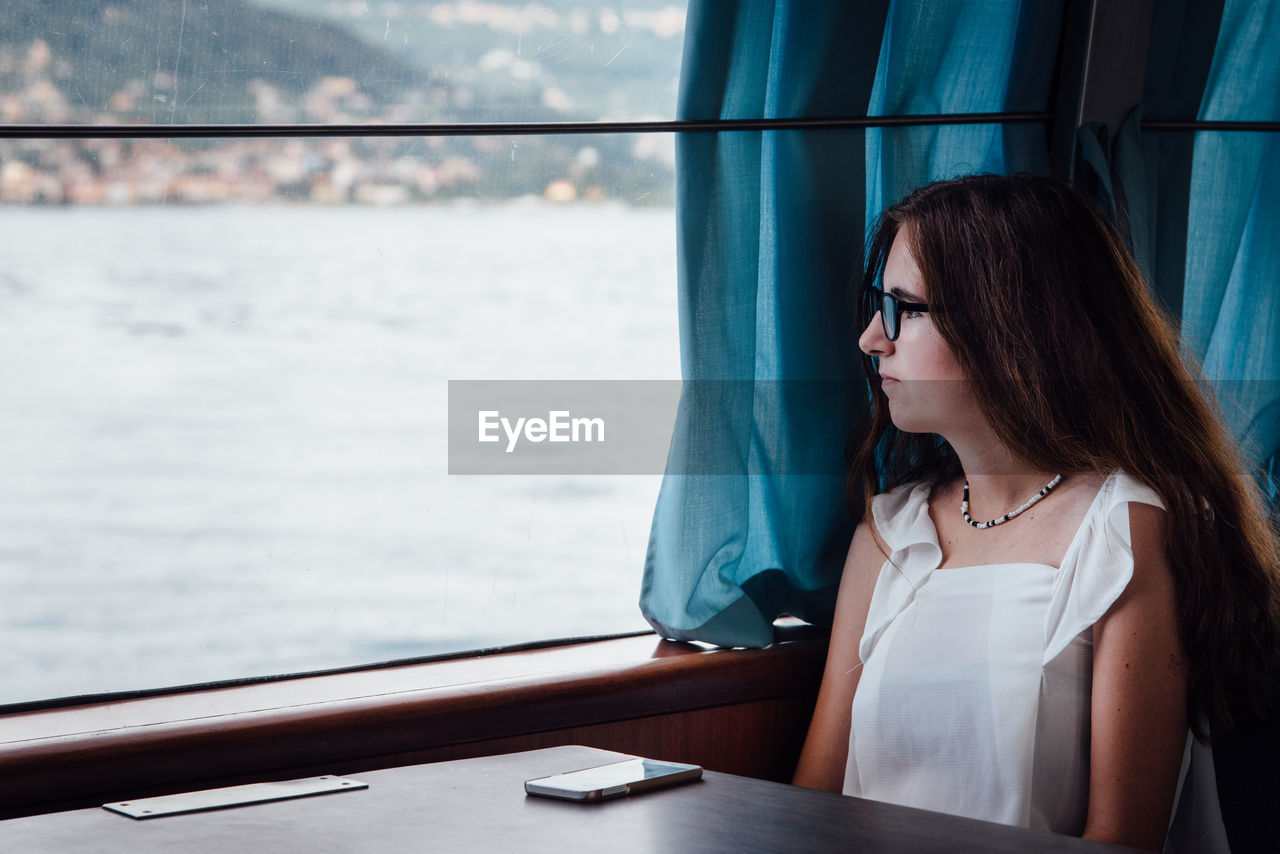Woman Sitting In Ferry Boat Looking Through Window
