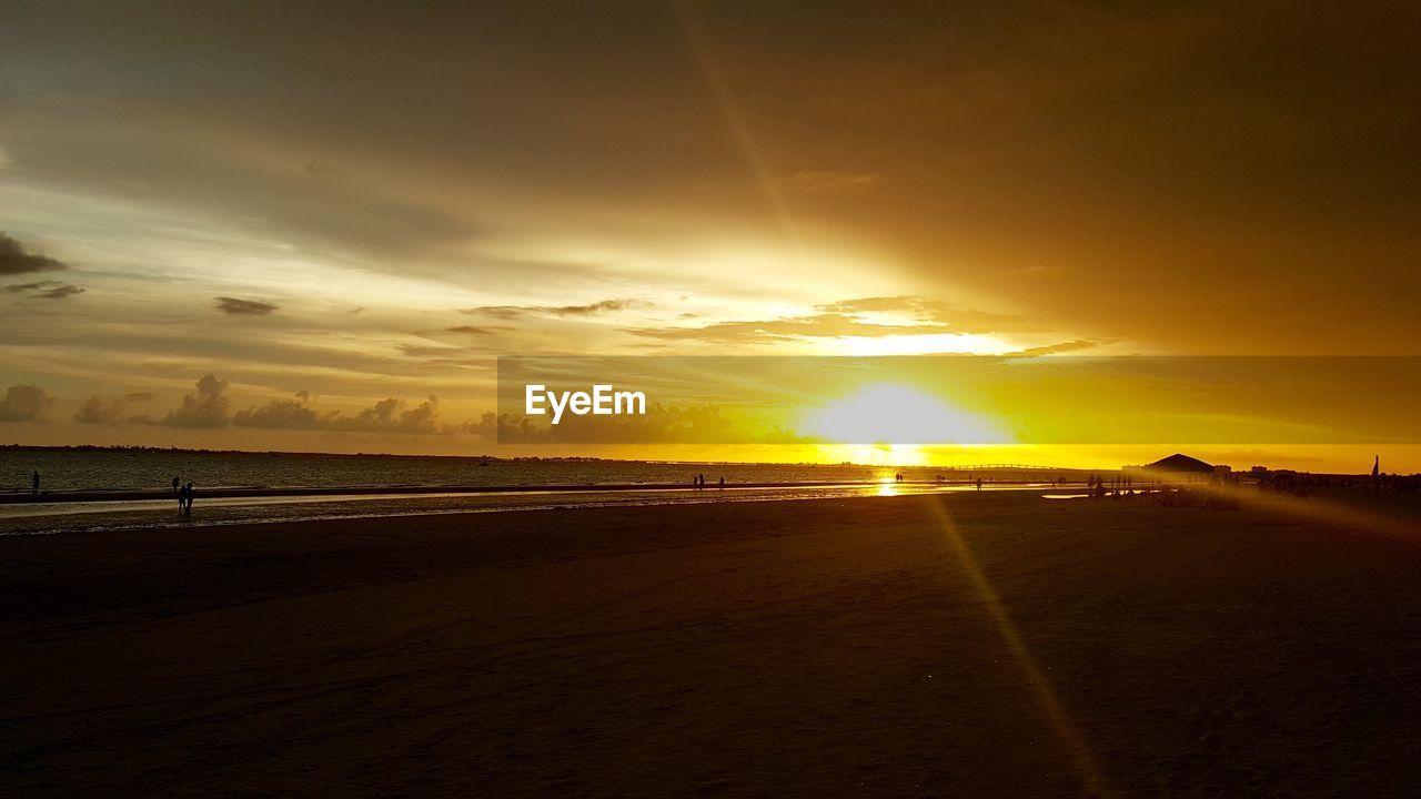 Beach against sky during sunset