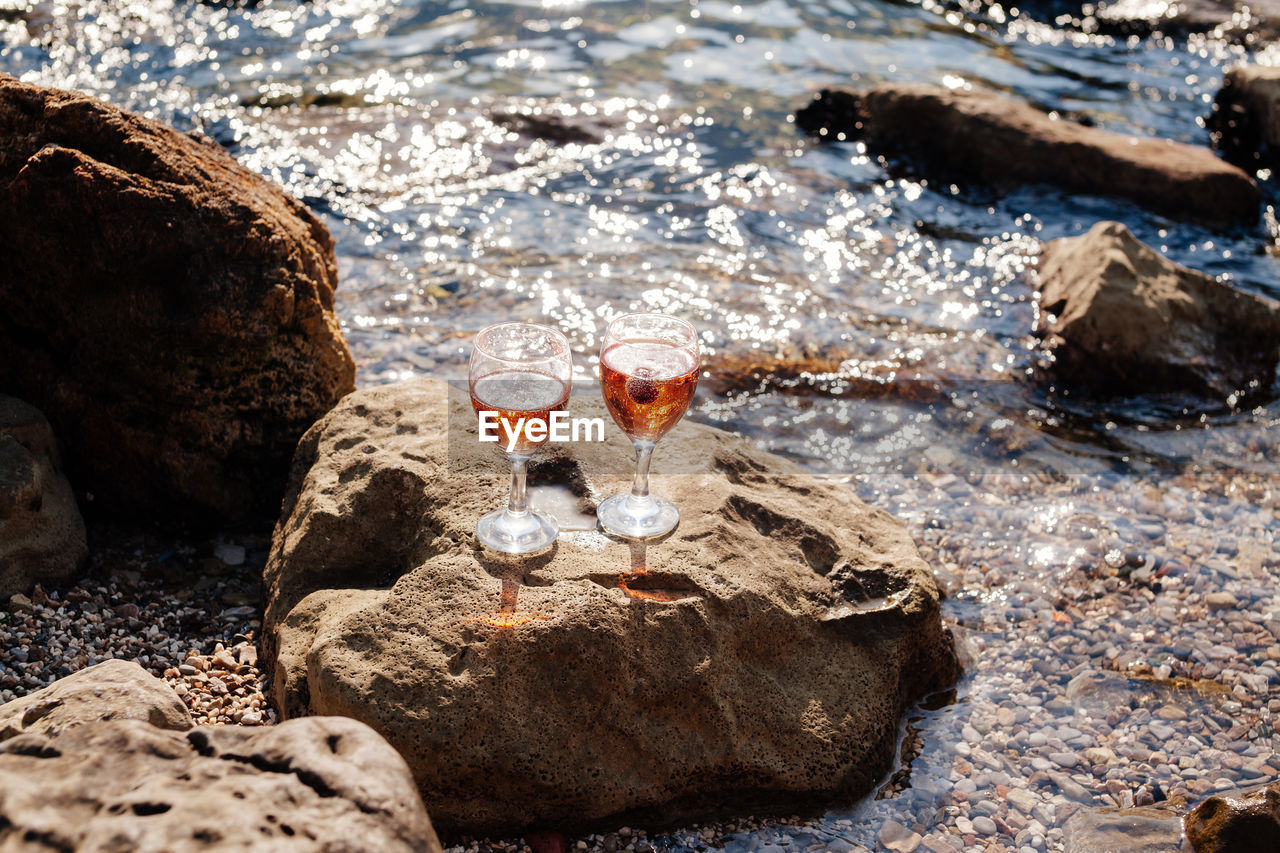 High Angle View Of Drinks On Rock At Beach