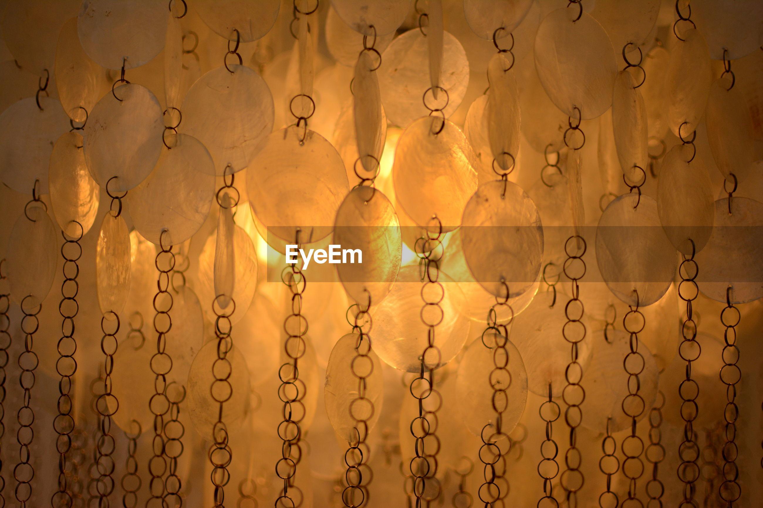 CLOSE-UP OF ILLUMINATED LIGHTING EQUIPMENT AGAINST WATER