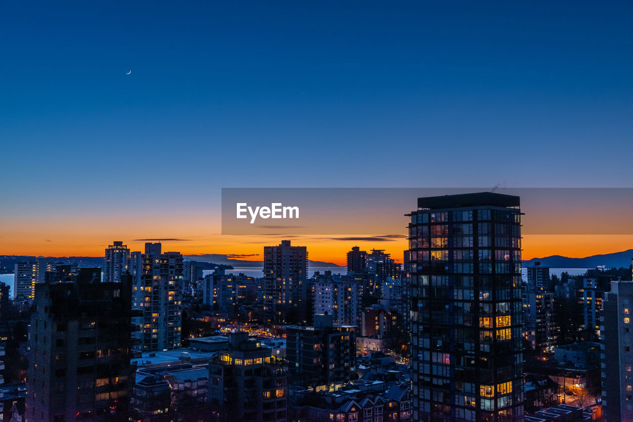 building exterior, sky, architecture, built structure, city, cityscape, sunset, building, orange color, copy space, residential district, no people, nature, office building exterior, skyscraper, tall - high, urban skyline, clear sky, illuminated, modern, outdoors, financial district, romantic sky