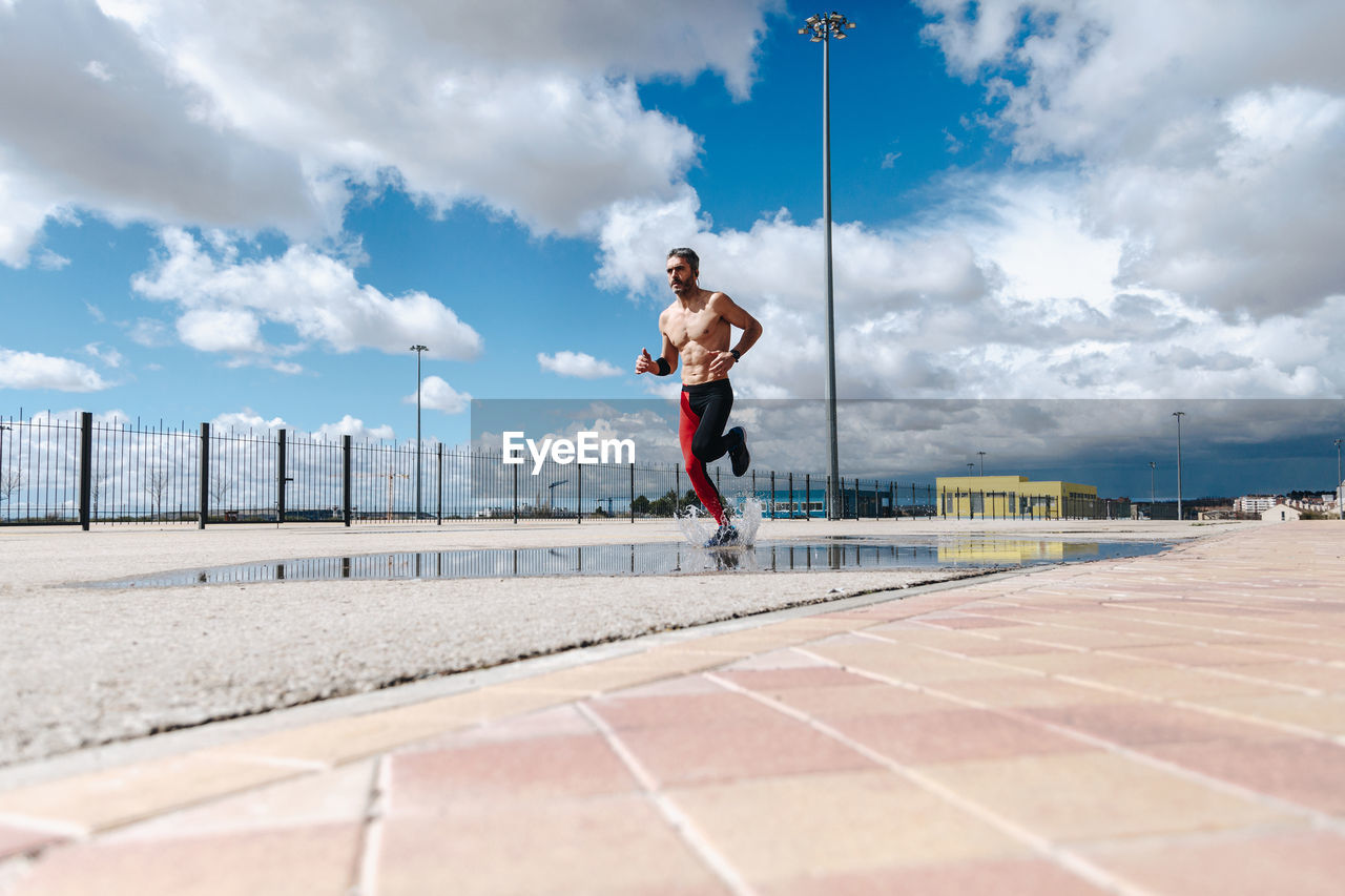 Mature Man Jogging On Road Against Cloudy Sky