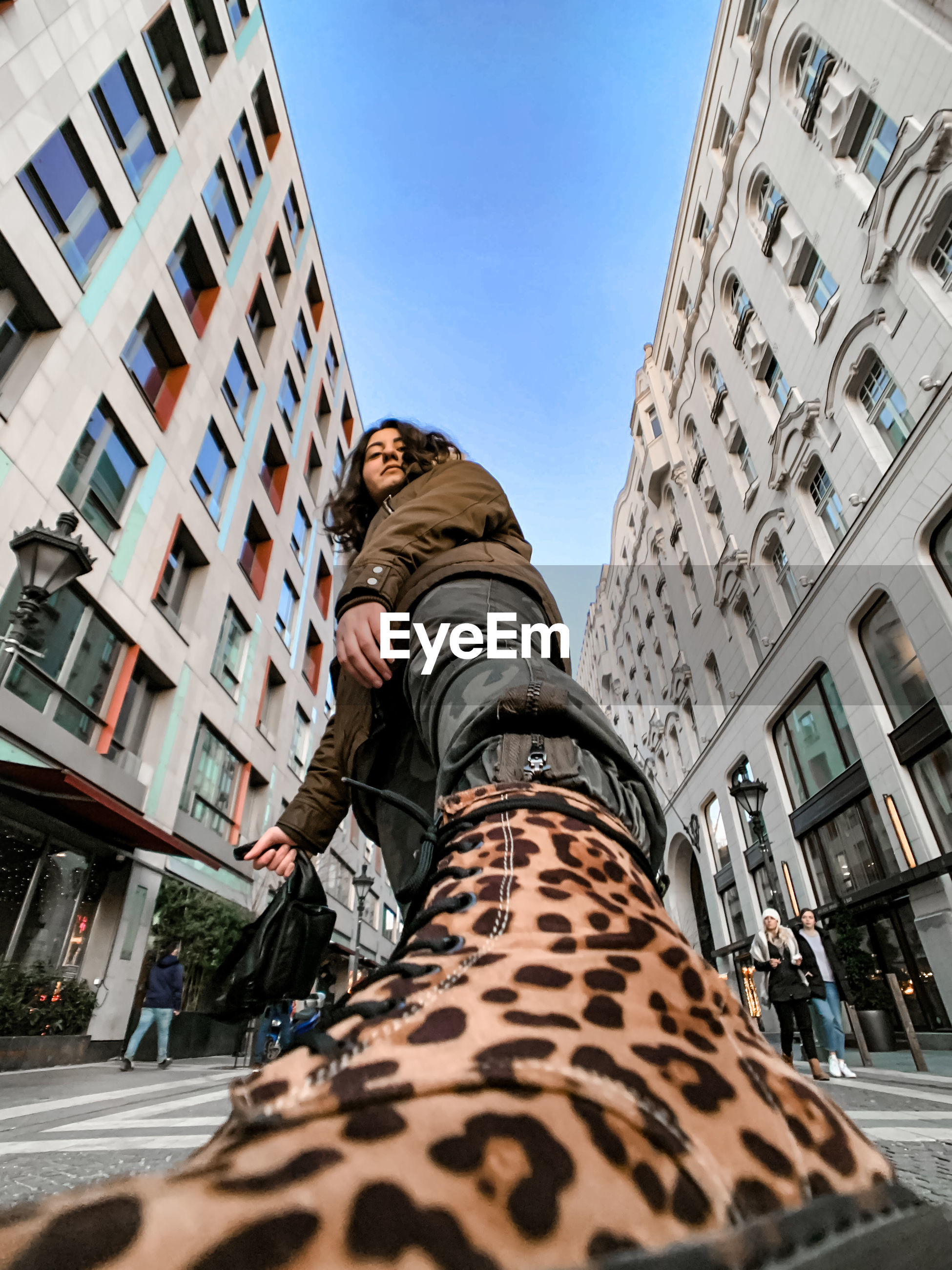 LOW ANGLE VIEW OF MAN AGAINST SKY IN CITY