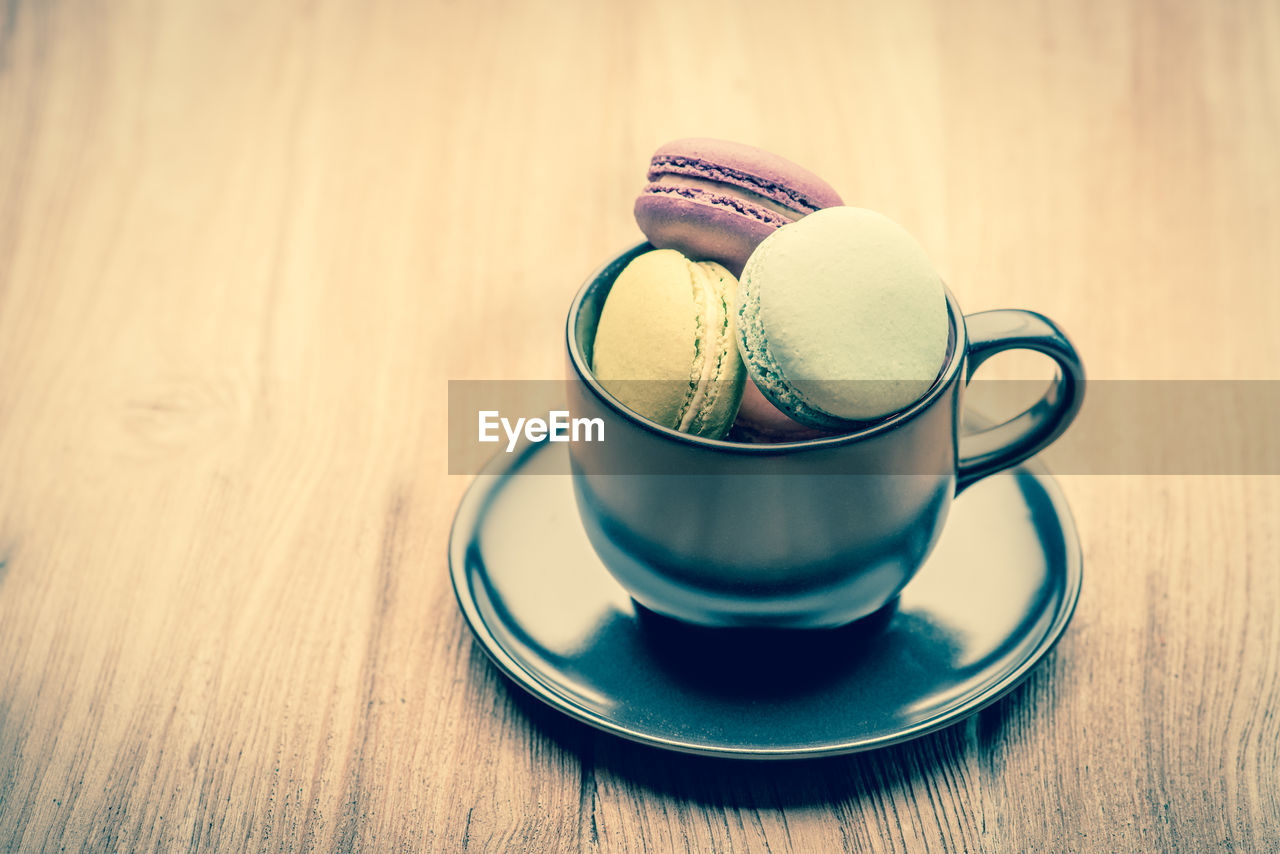 table, food and drink, saucer, crockery, still life, wood - material, indoors, cup, sweet food, mug, drink, food, close-up, no people, coffee cup, coffee - drink, kitchen utensil, coffee, refreshment, sweet, temptation, macaroon, tea cup