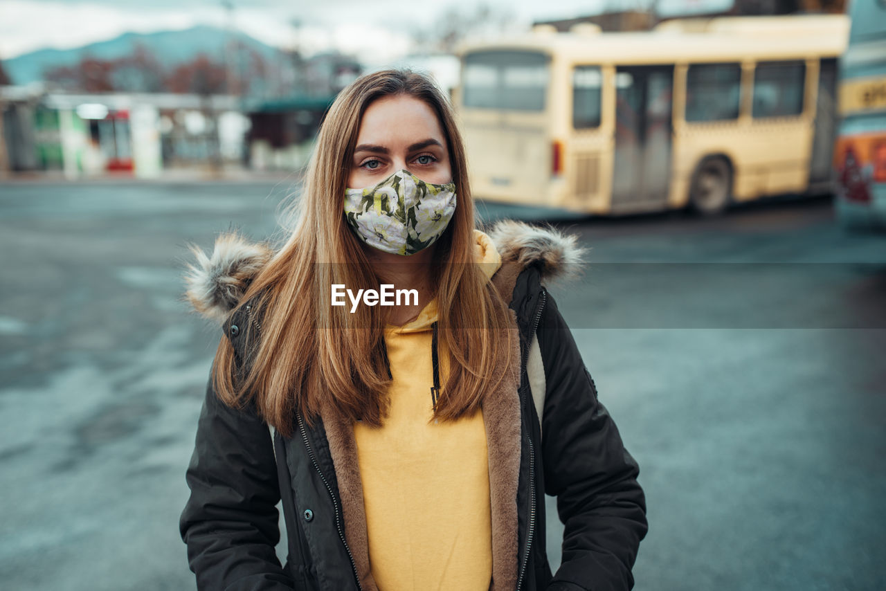 Portrait of young woman wearing mask standing in city during winter