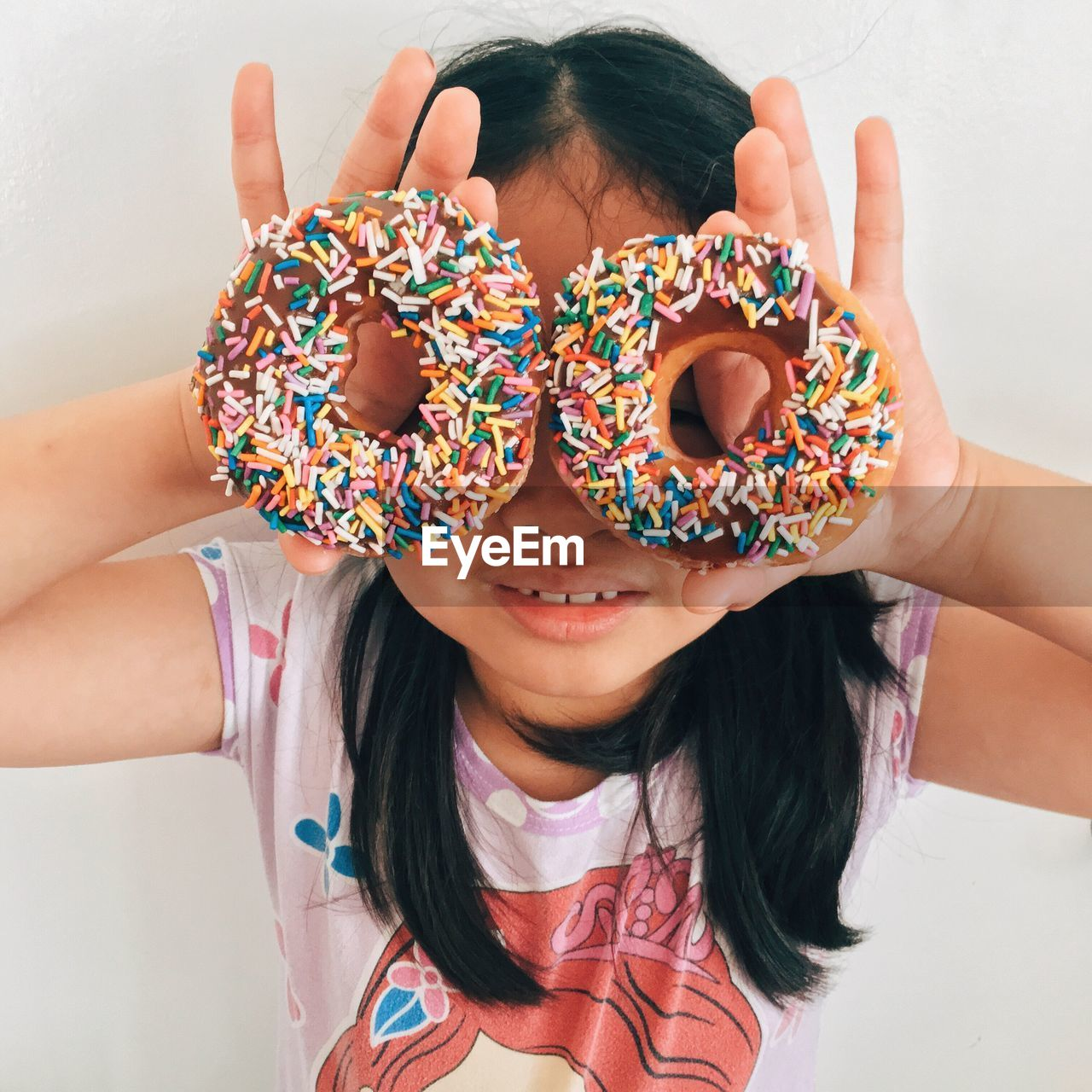 High Angle View Of Girl Holding Doughnuts In Front Of Her Face