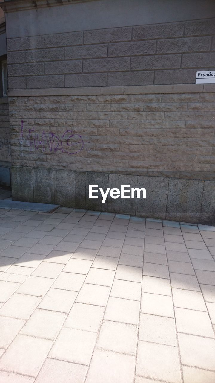 built structure, architecture, wall - building feature, flooring, tile, no people, footpath, tiled floor, empty, building exterior, day, subway, text, building, pattern, city, wall, outdoors, absence, brick, paving stone, garage, underpass