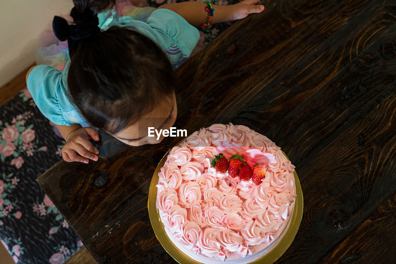 High angle view of girl by cake