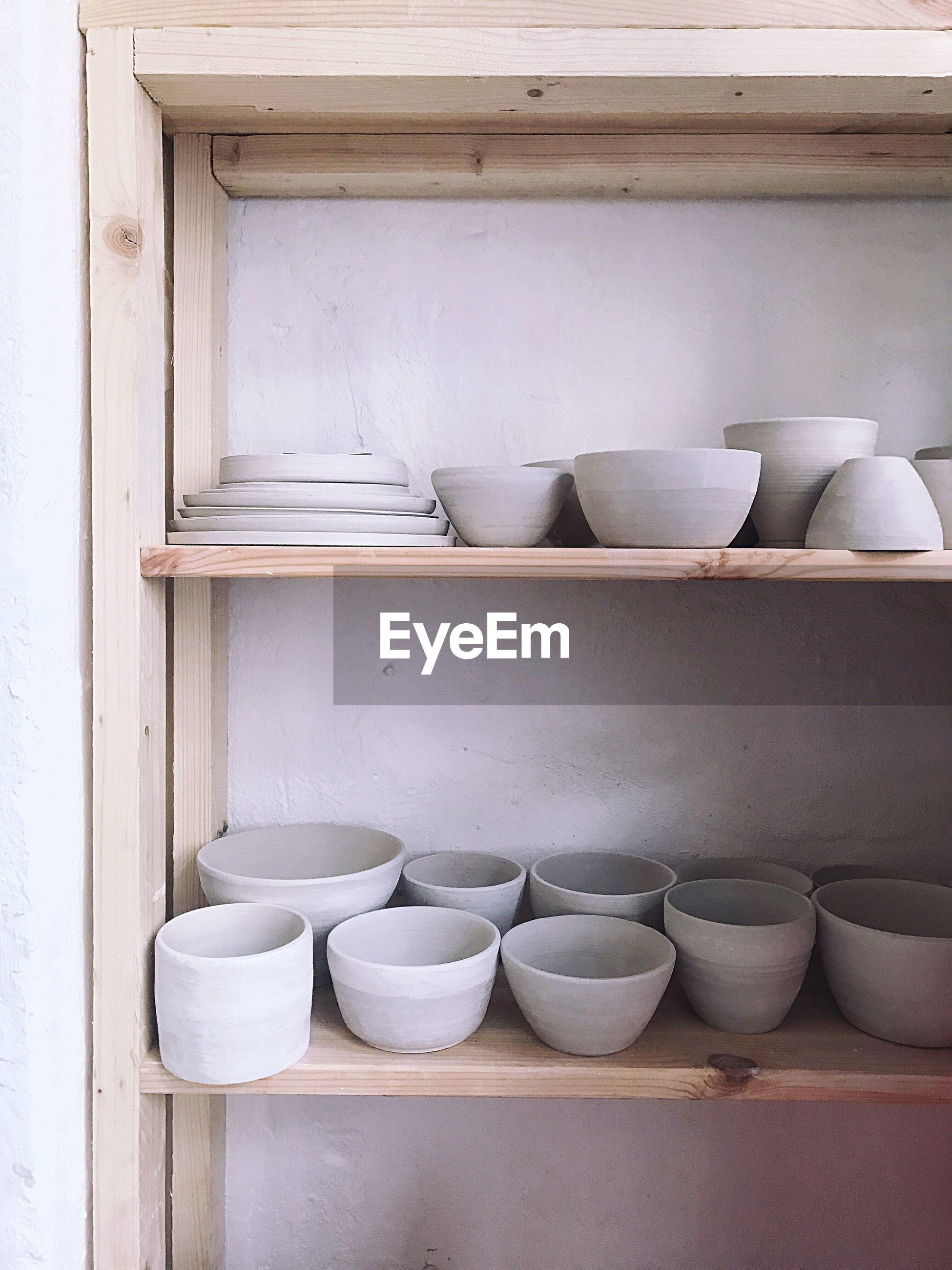 Crockery in shelf against wall