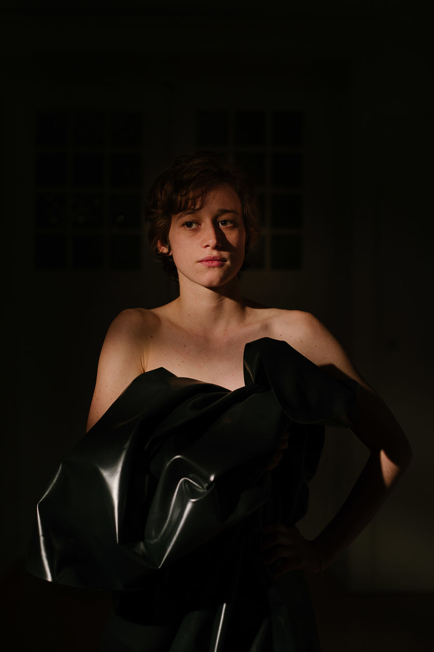 Thoughtful young woman standing in darkroom