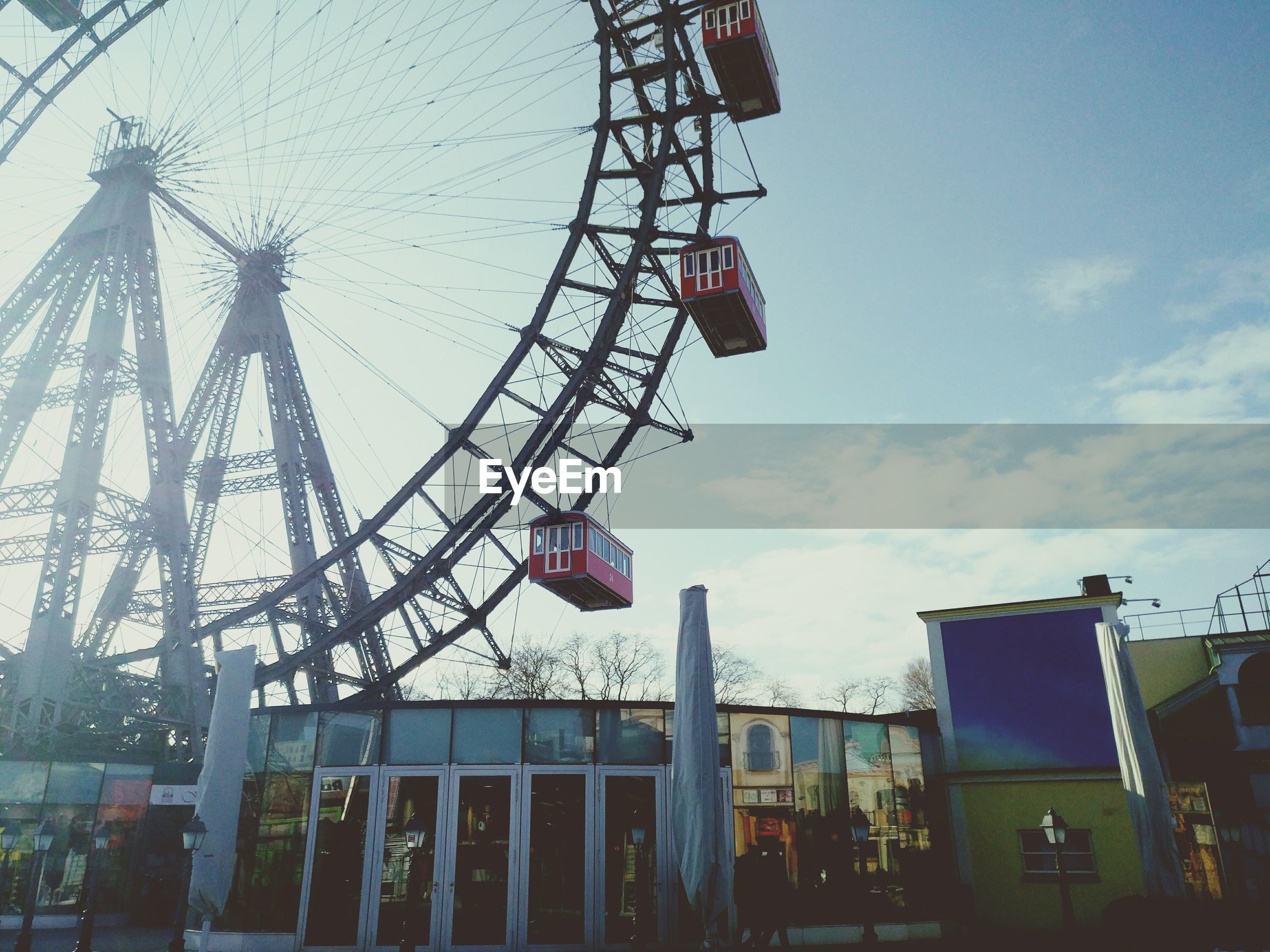 amusement park, low angle view, arts culture and entertainment, sky, ferris wheel, amusement park ride, leisure activity, outdoors, tree, day, no people, big wheel