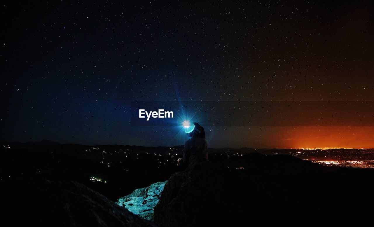 Silhouette Woman With Illuminated Flashlight Against Star Field