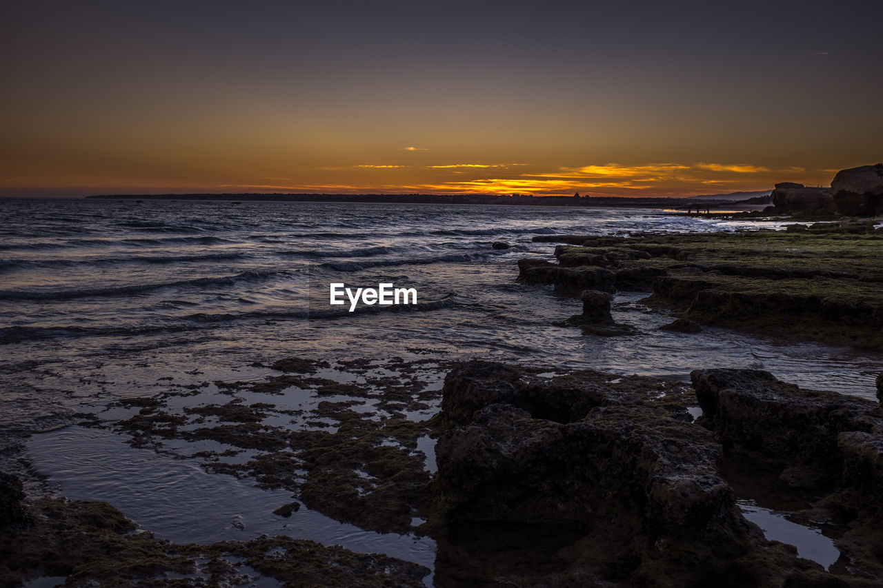 sky, sunset, water, sea, scenics - nature, beauty in nature, rock, beach, tranquility, orange color, nature, solid, rock - object, tranquil scene, land, no people, cloud - sky, idyllic, non-urban scene, horizon over water, outdoors, rocky coastline