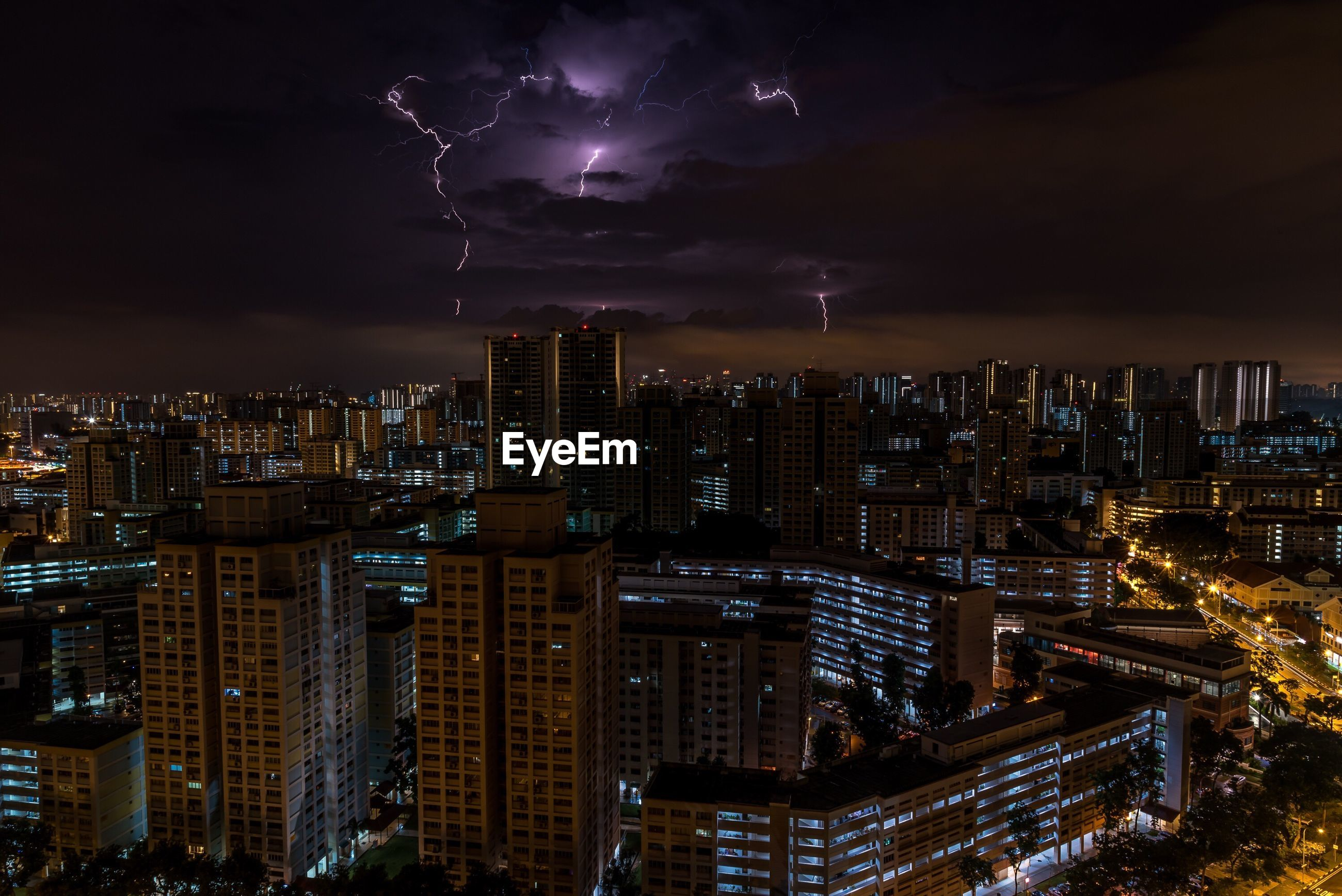 AERIAL VIEW OF ILLUMINATED CITY AGAINST CLOUDY SKY