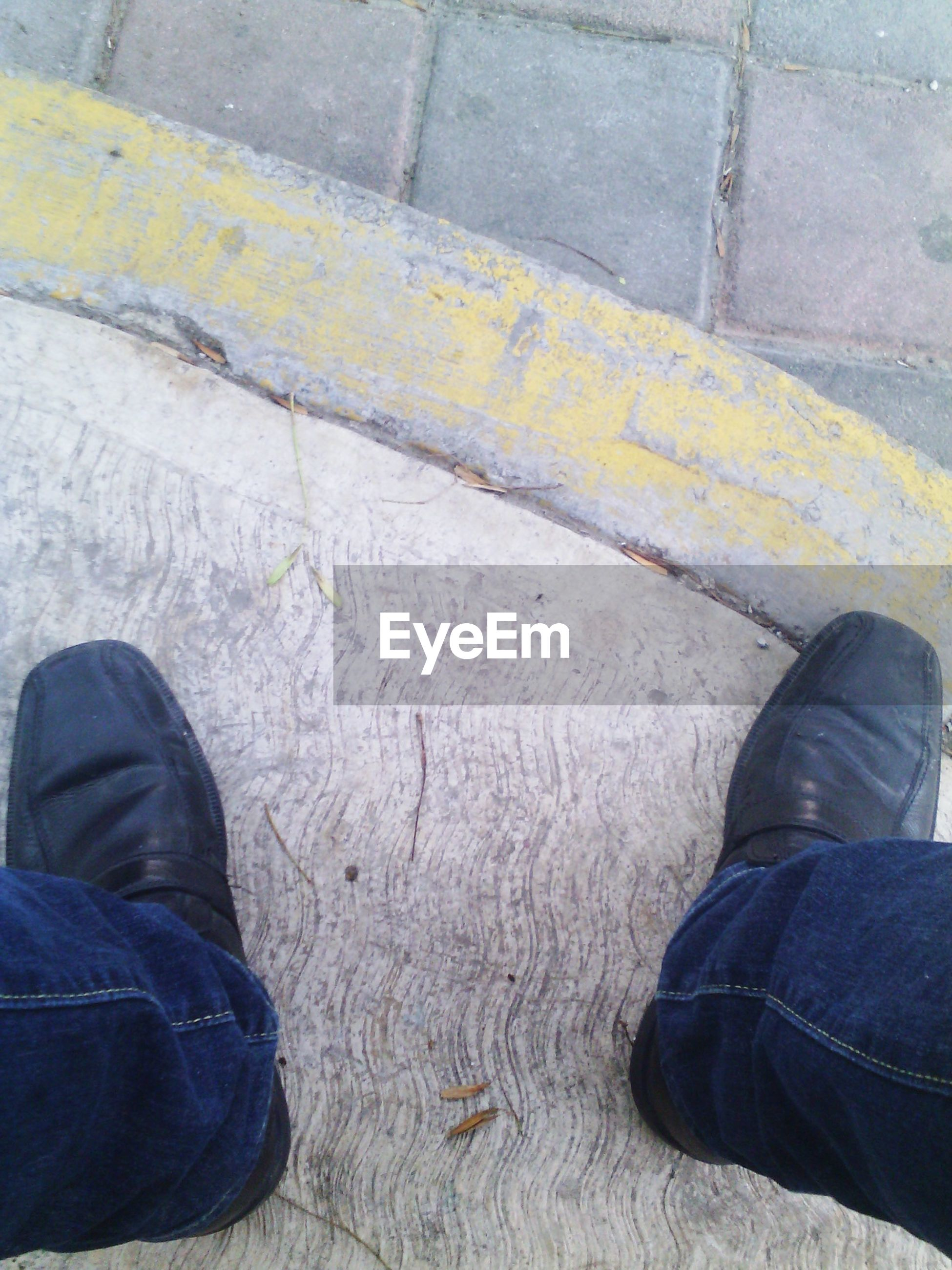 standing, personal perspective, shoe, person, low section, men, high angle view, human foot, jeans, footwear, lifestyles, directly above, human limb, leisure activity, street, limb, casual clothing, adult, pants, day, canvas shoe, footpath