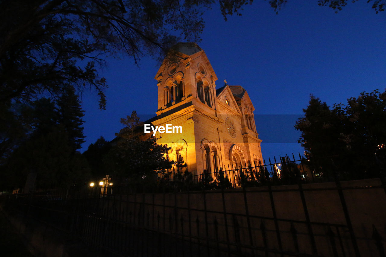 Low Angle View Of Church And Silhouette Trees At Dusk