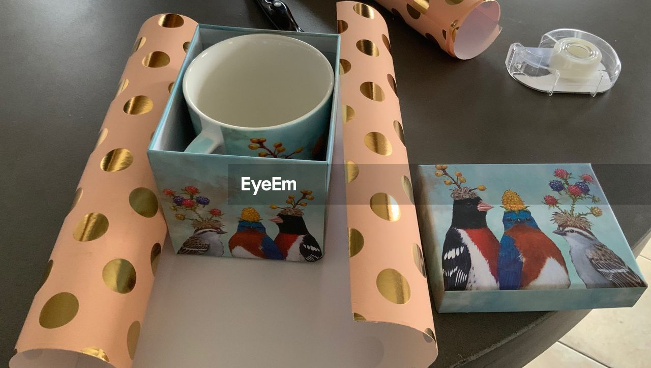 table, indoors, still life, high angle view, art and craft, no people, cup, food and drink, pattern, mug, multi colored, drink, representation, container, creativity, decoration, animal representation, design, craft, ceramics, box - container, floral pattern, crockery, tray