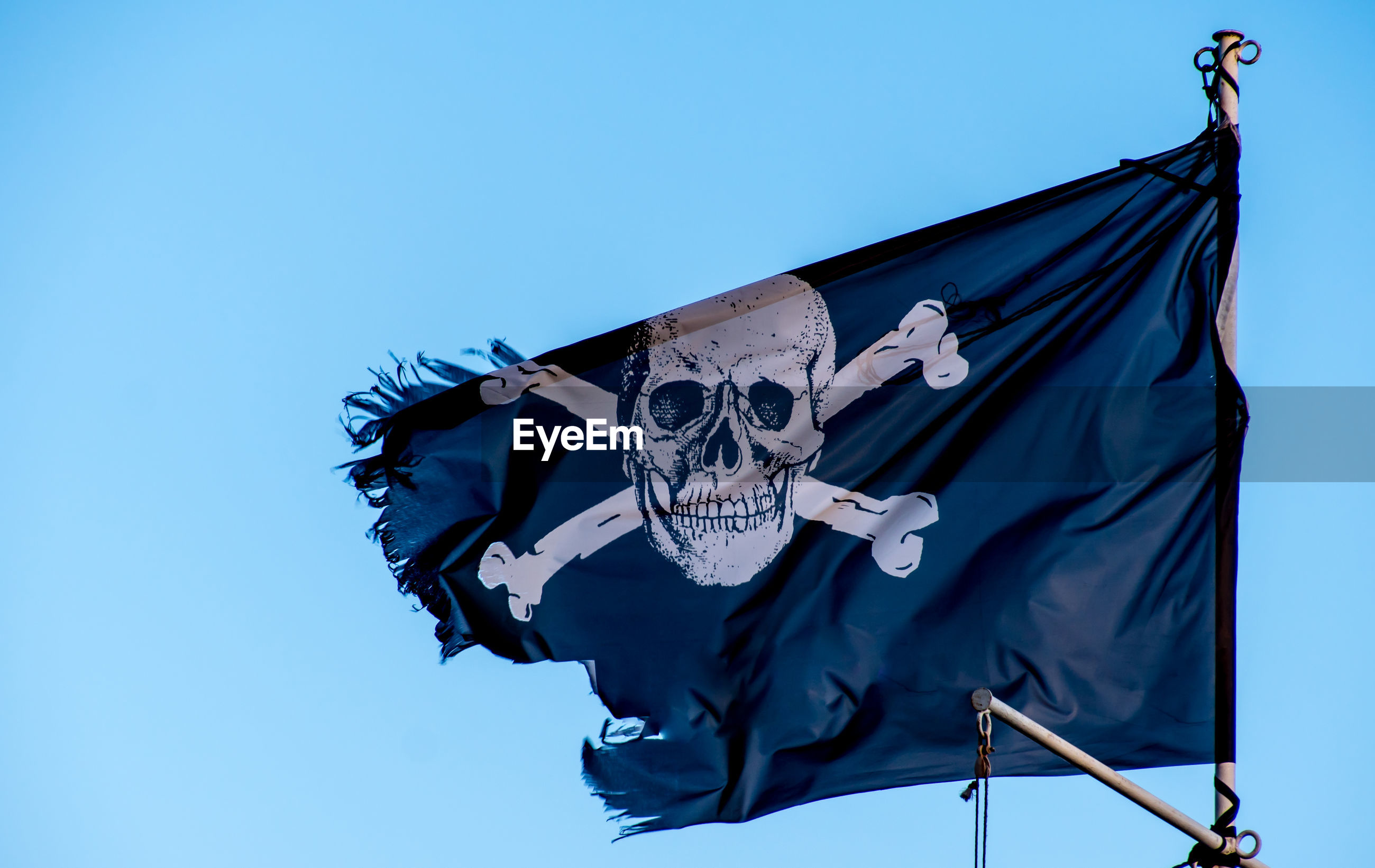 Pirate flag waving against clear blue sky