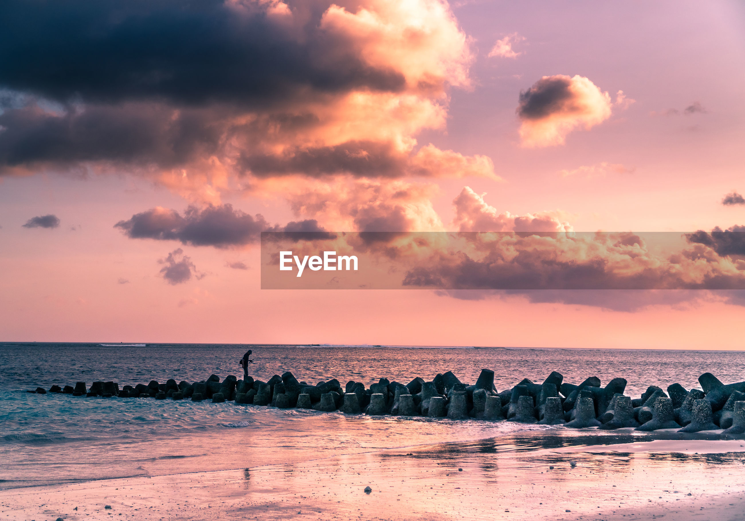 Person standing on tetrapods at beach against sky during sunset