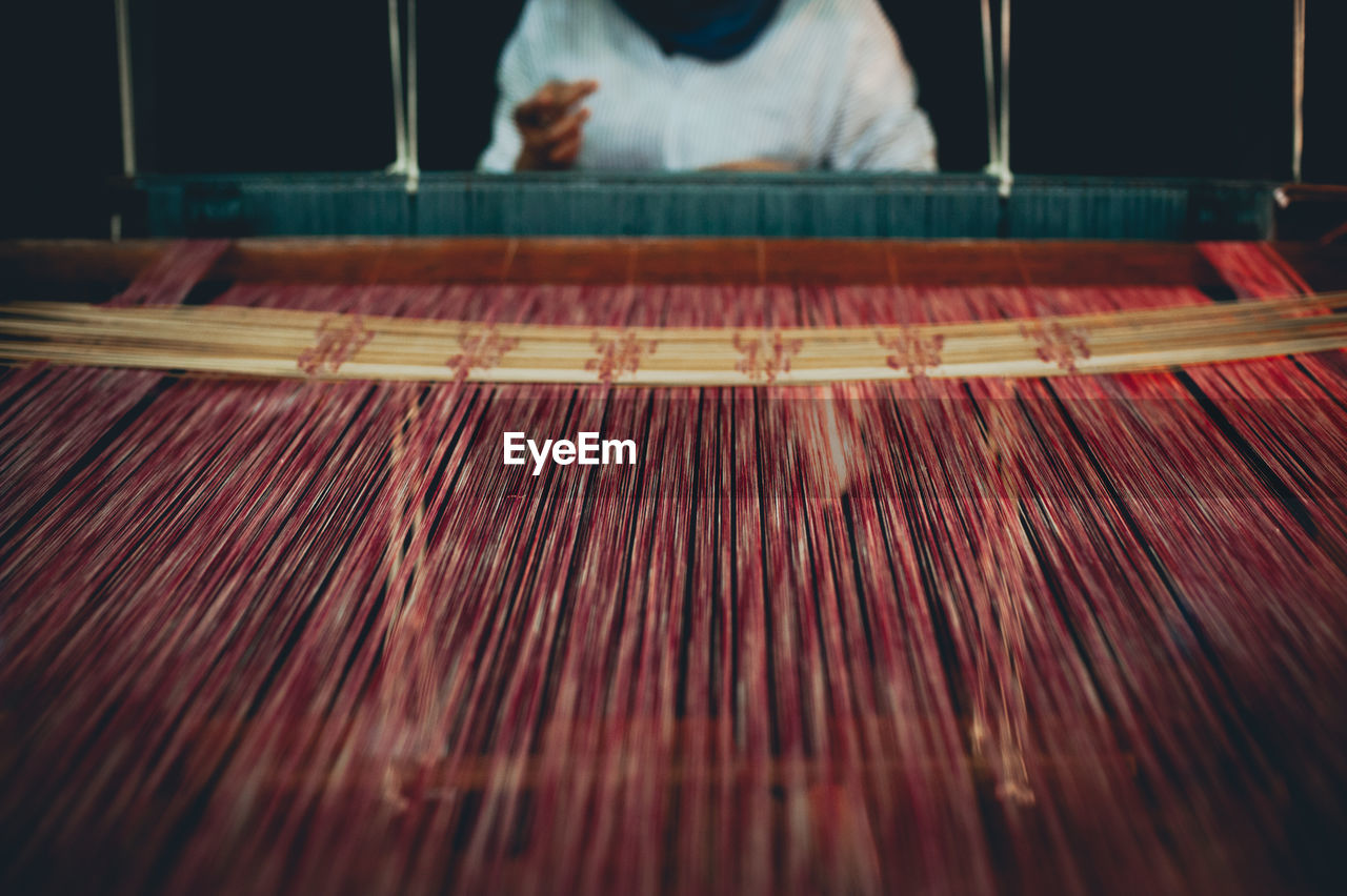 Midsection Of Woman Weaving Loom At Factory