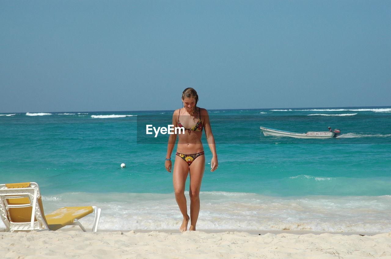 Woman In Bikini Walking On Shore At Beach Against Clear Sky