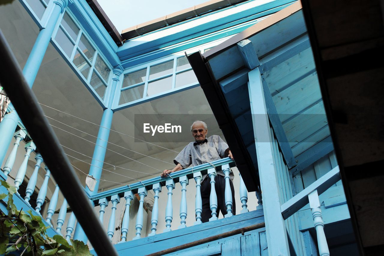 Low angle view of man looking over banister