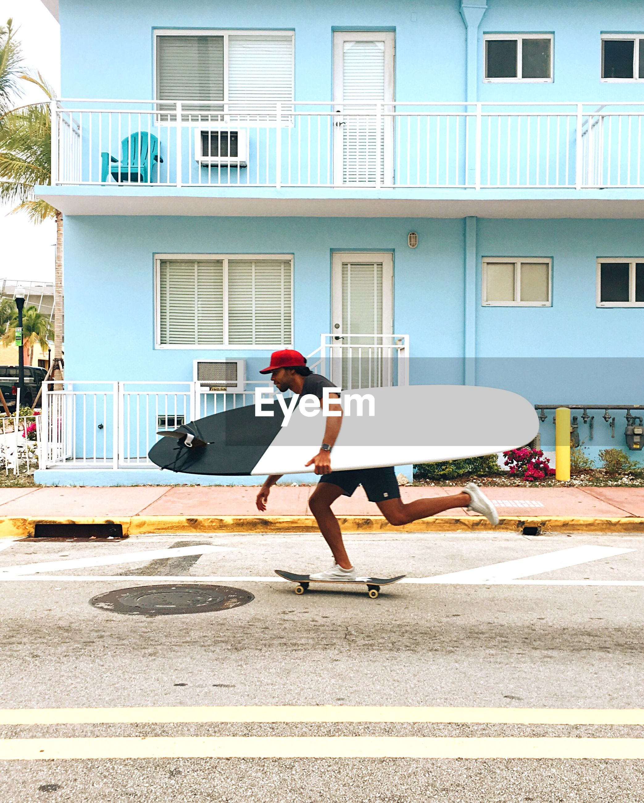 SIDE VIEW OF MAN SKATEBOARDING ON ROAD AGAINST BUILDINGS