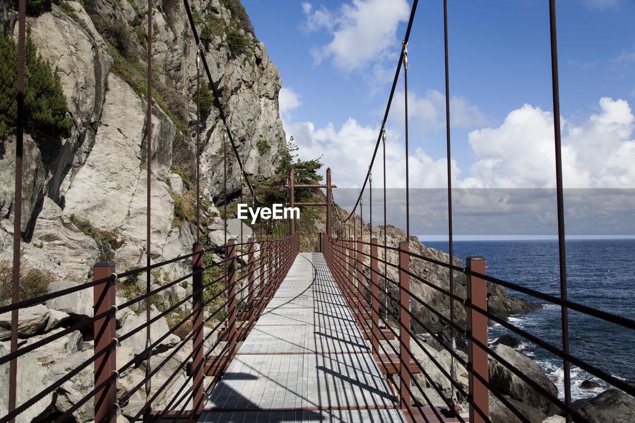 Footbridge By Mountain Against Cloudy Sky