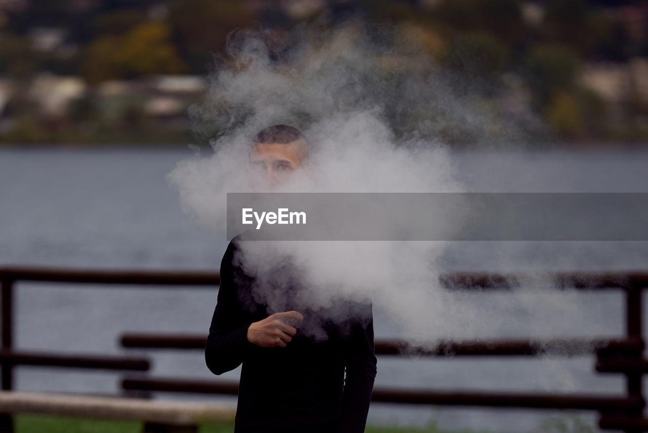 Teenage boy smoking while holding electronic cigarette against lake