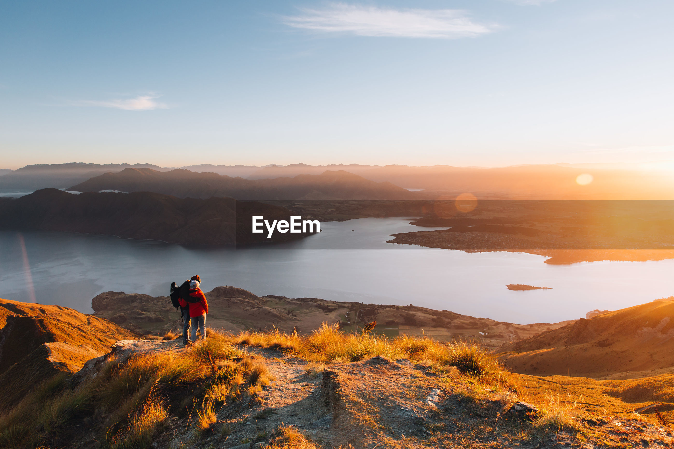 Couple standing on mountains against sky during sunset
