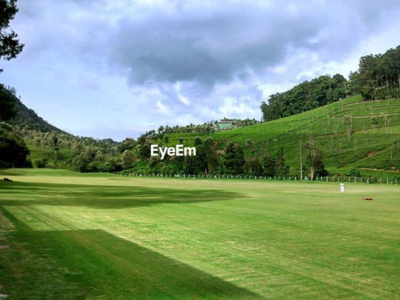 golf course, golf, green - golf course, tree, green color, sport, cloud - sky, scenics, nature, grass, landscape, sand trap, beauty in nature, no people, tourist resort, mountain, vacations, day, travel destinations, sky, outdoors