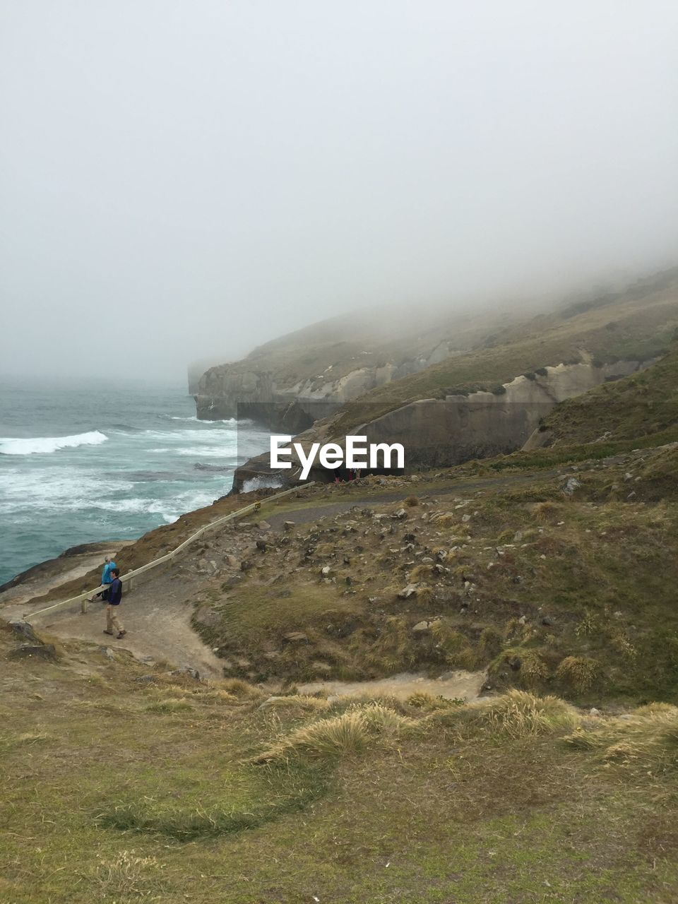 Tourists On Cliff By Sea At Tunnel Beach During Foggy Weather