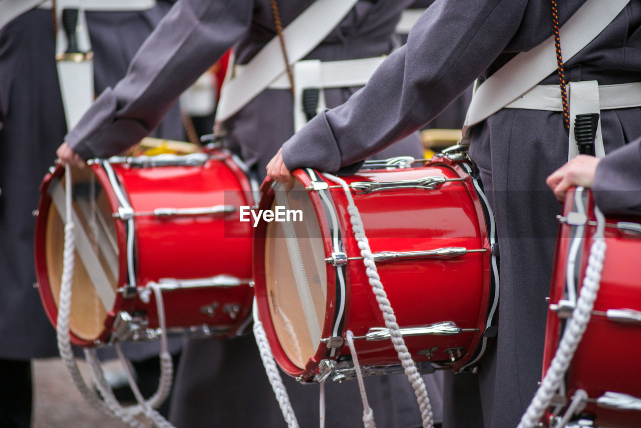 red, midsection, real people, drum - percussion instrument, day, musical instrument, musical equipment, music, human body part, focus on foreground, outdoors, men, people, incidental people, arts culture and entertainment, city, celebration, drum, two people, marching band
