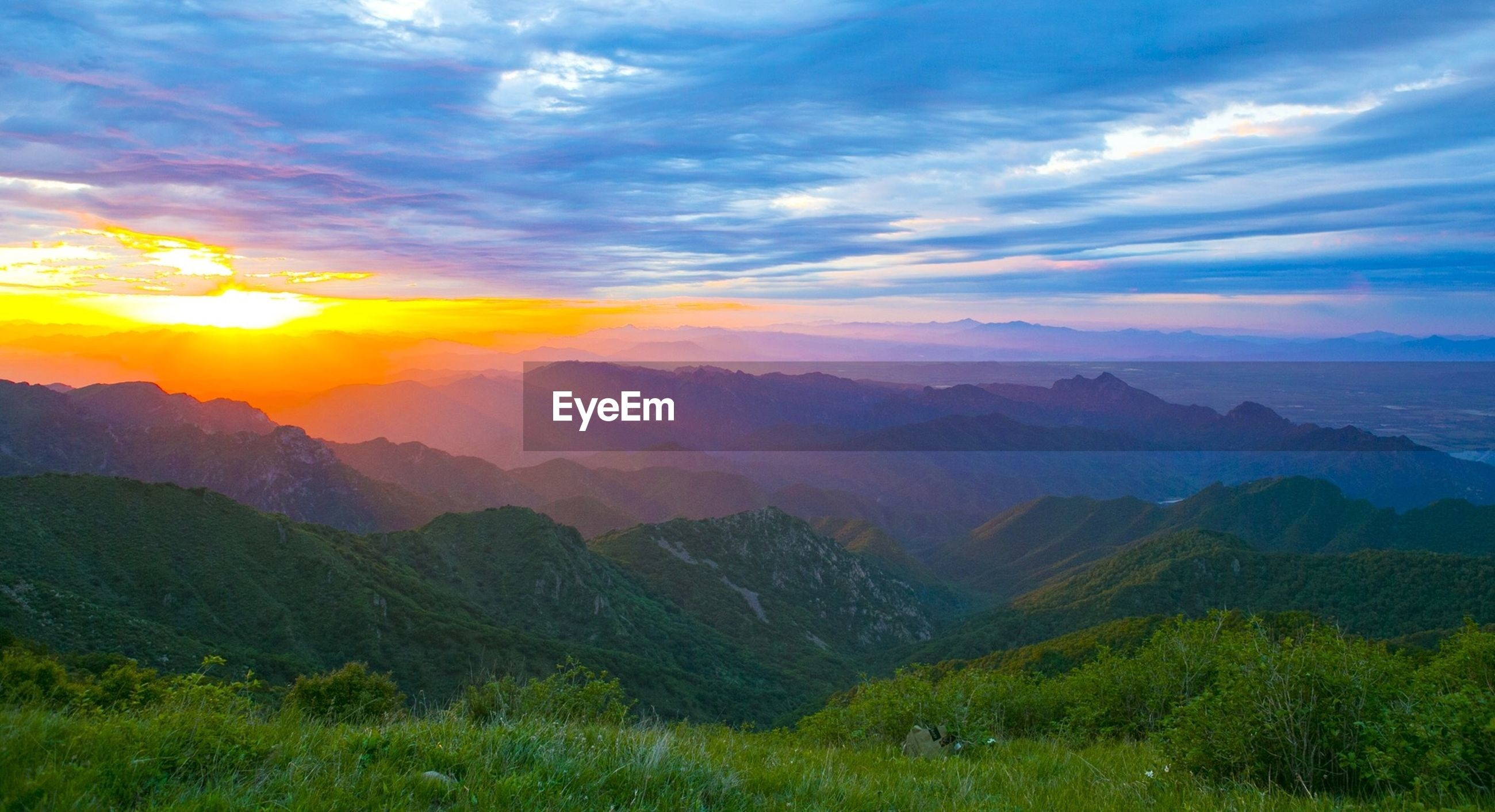 tranquil scene, scenics, mountain, tranquility, beauty in nature, landscape, sky, sunset, mountain range, nature, cloud - sky, idyllic, cloud, non-urban scene, sun, sunlight, field, grass, sunbeam, outdoors