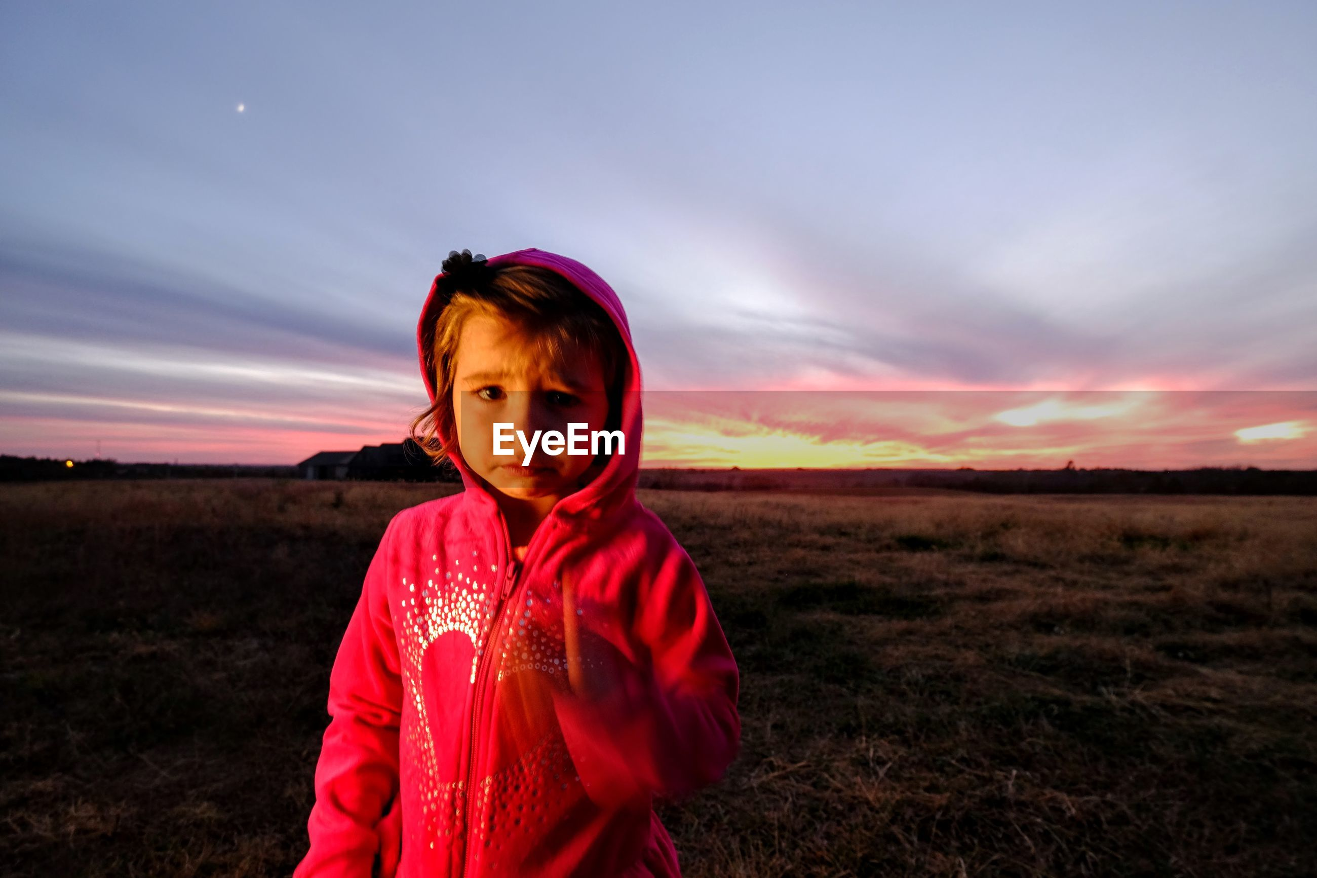 Portrait of girl standing on field against sky during sunset