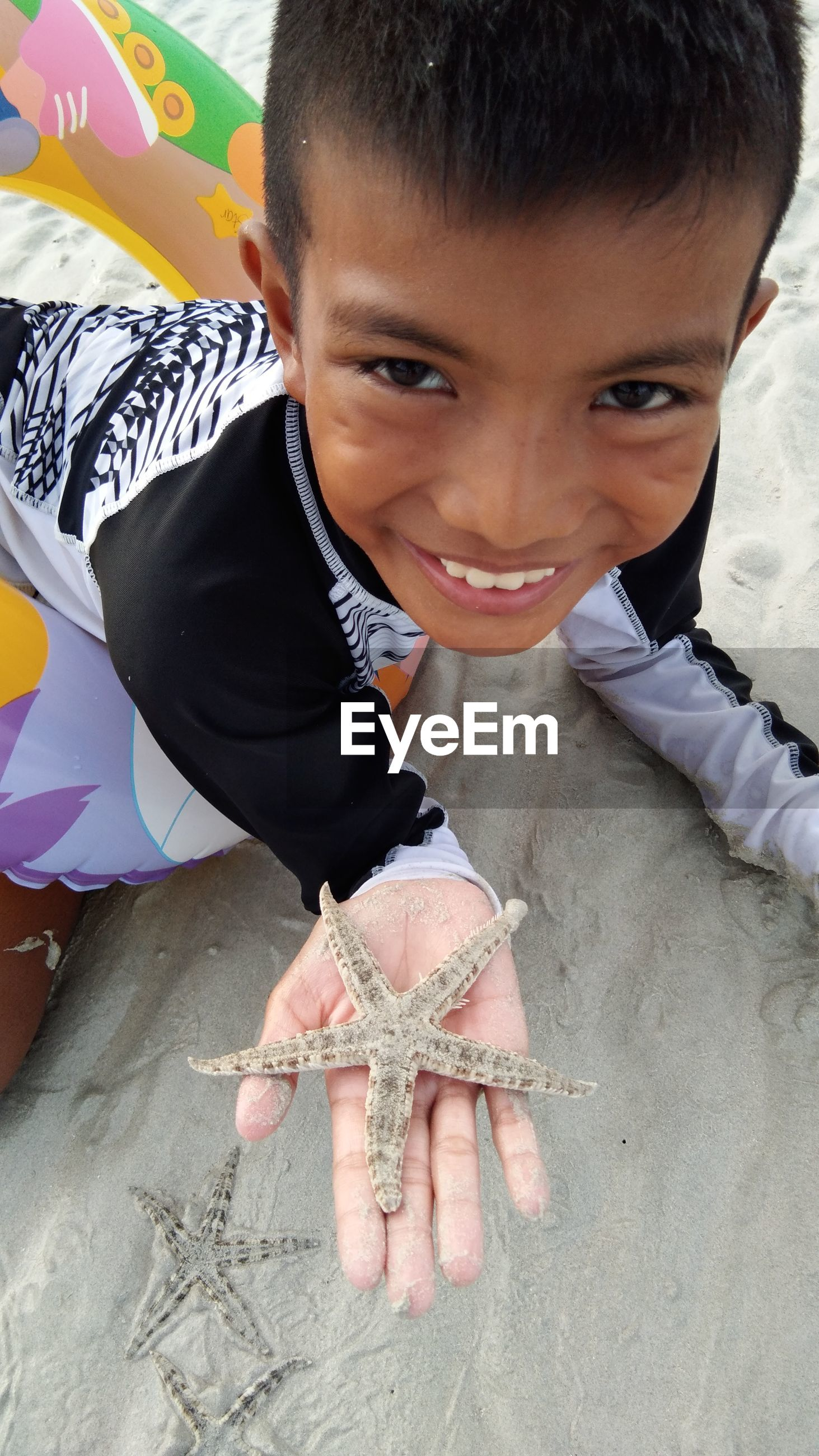 High angle portrait of smiling boy holding starfish on sand at beach